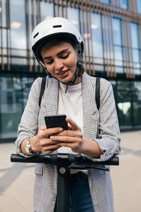 Young woman with a safety helmet leaning on an electrical scooter typing on her cell phone