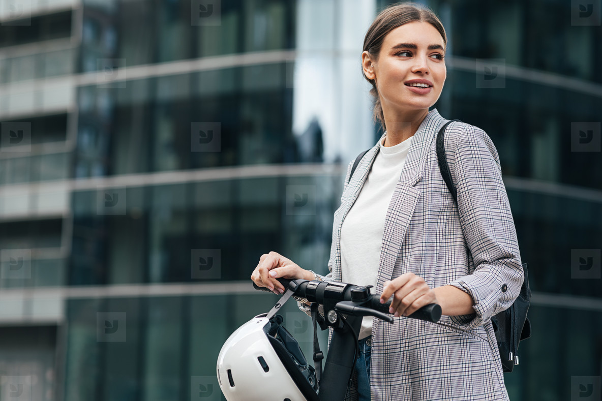 Portrait of a caucasian businesswoman with an electrical scooter  Smilaing female holding a scooter looking away in front of an office building