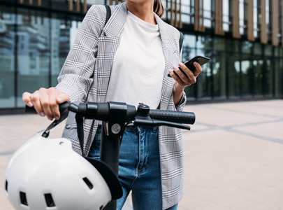 Unrecognizable businesswoman standing in front of an office building with electrical scooter and holding a smartphone