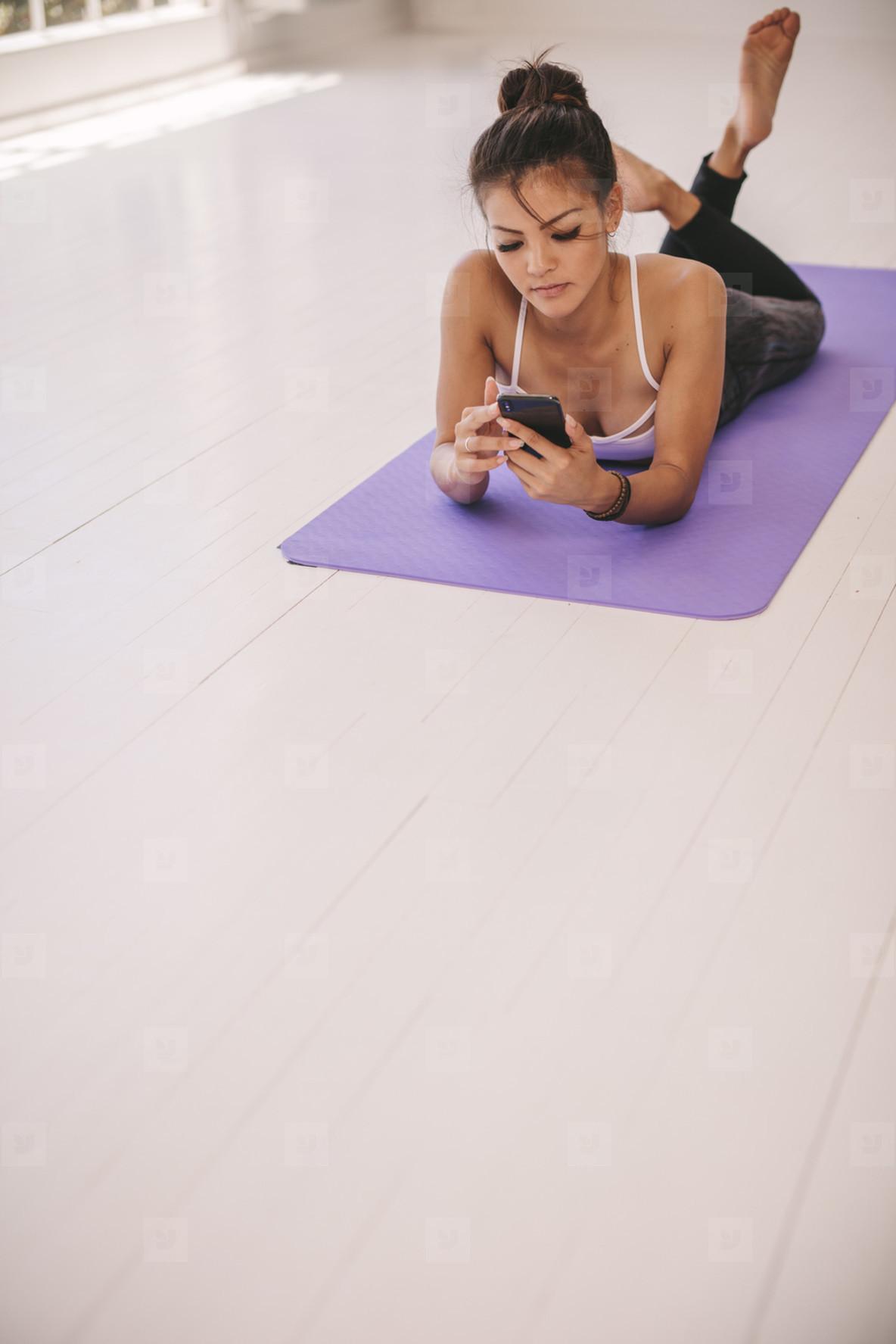Woman lying on yoga mat using mobile phone