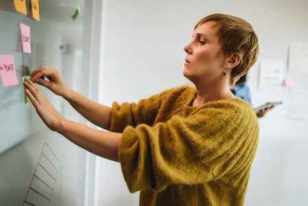 Female executive putting sticky note on glass