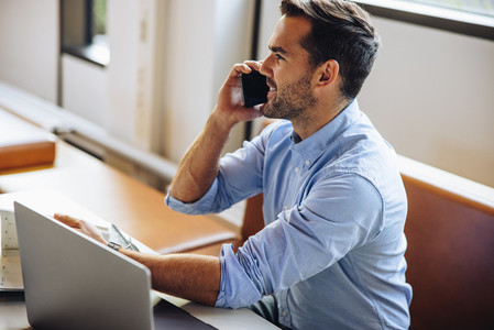 Businessman at desk talking on cell phone