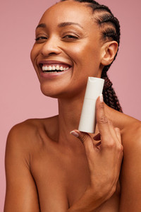 Smiling woman presenting beauty product