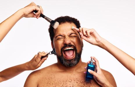 Bearded man groomed by many hands
