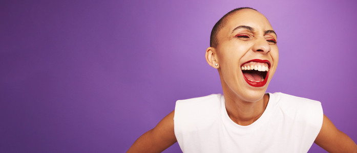 Woman with short hairstyle laughing on purple background