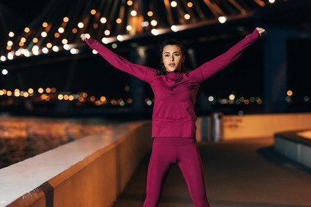Young middle eastern woman in sports clothes doing warming up exercises outdoors