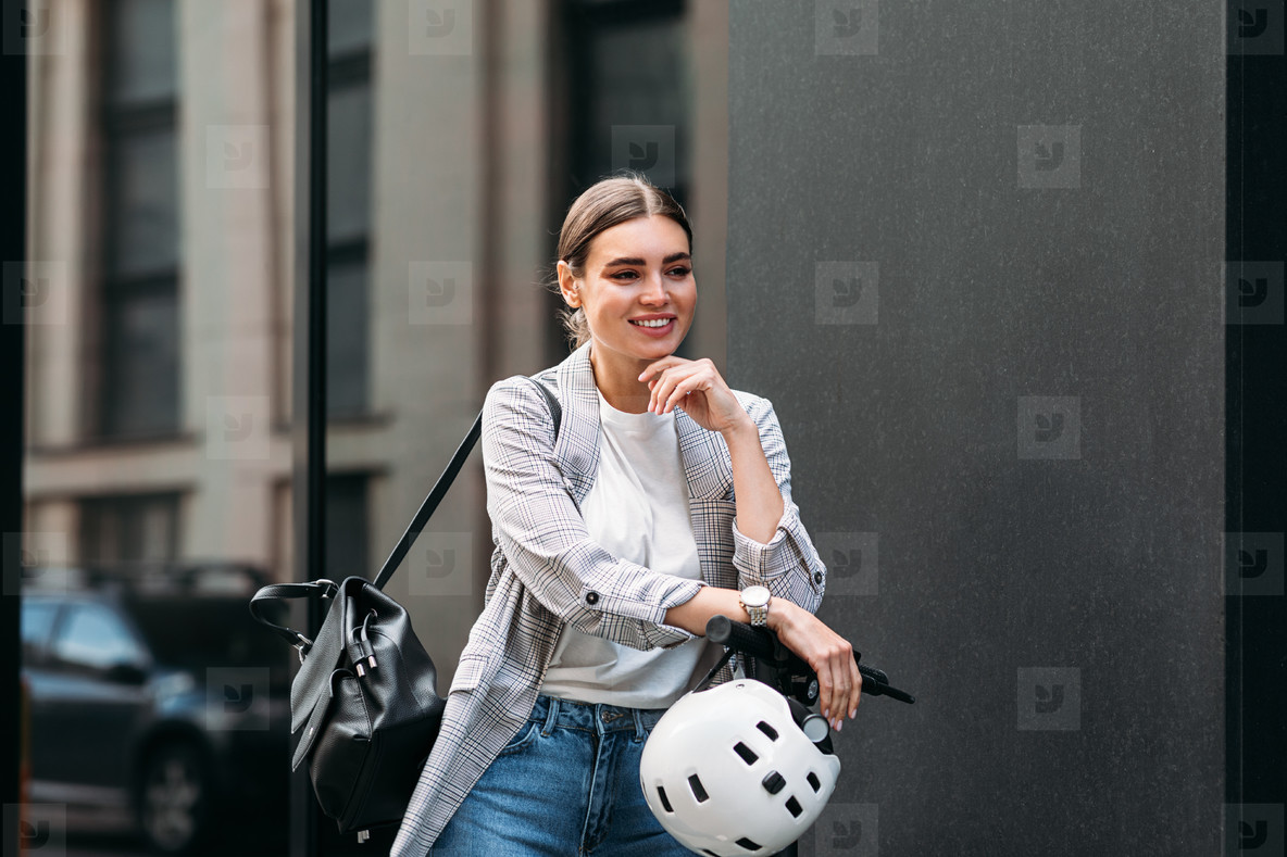 Smiling confident woman with an electrical scooter  safety helmet  and backpack standing at the building
