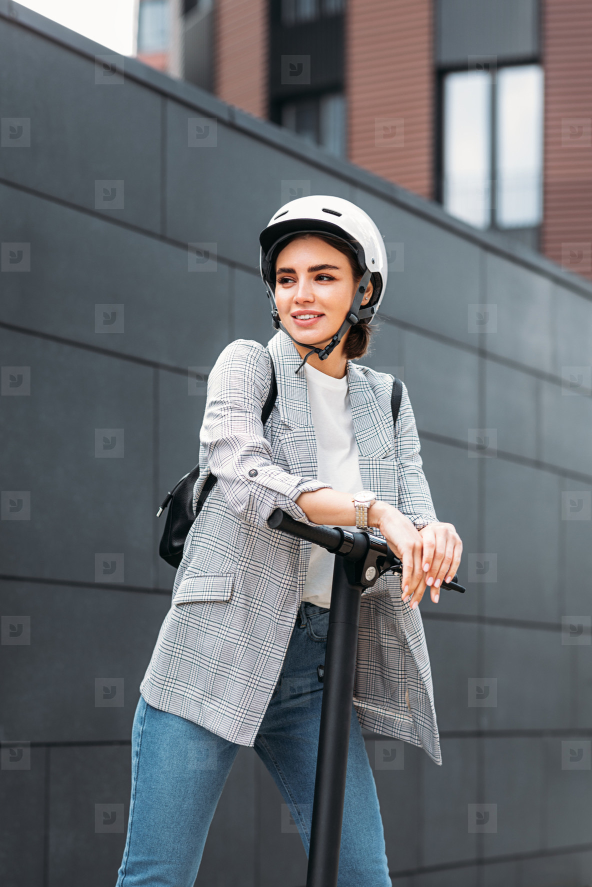Businesswoman leaning on electric scooter and looking away  Portrait of young female holding scooter outdoors