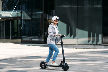 Young businesswoman with a safety helmet on her head driving electrical scooter near an office building