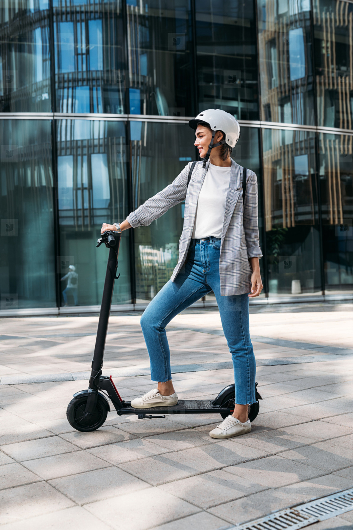 Side view young woman standing on electrical scooter near an office building  Female in helmet ready for a ride on scooter