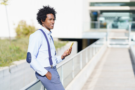 Black man with afro hairstyle using a smartphone near an office building