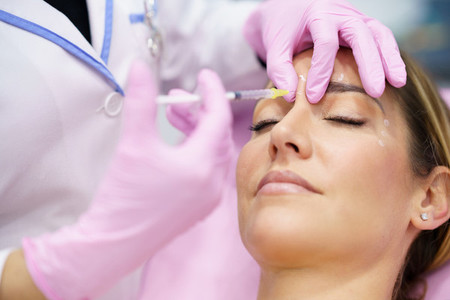 Aesthetic doctor injecting botulinum toxin into the forehead of her middle aged patient
