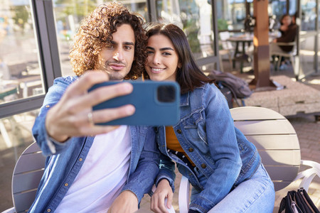 Arab couple taking selfie pictures with their smartphone  sitting on the terrace of a bar