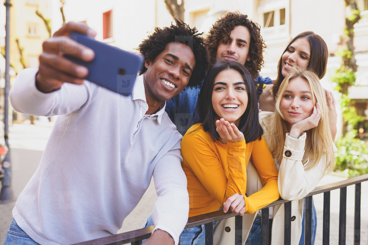 Black man with afro hair taking a smartphone selfie with his multi ethnic group of friends
