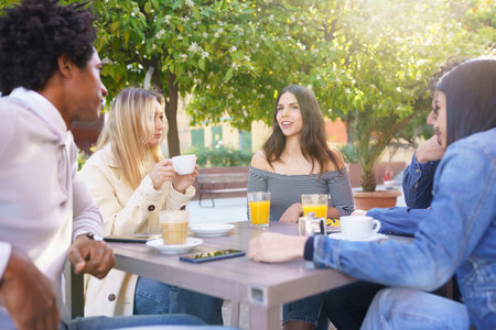 Multi ethnic group of students having a drink on the terrace of a street bar