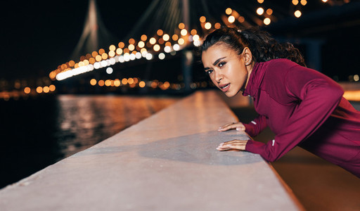 Young mixed race female athlete doing push ups on an embankment at evening
