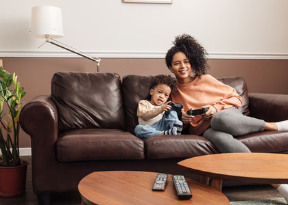 Young mother and her little son sitting on a couch in the living room playing video games on a console