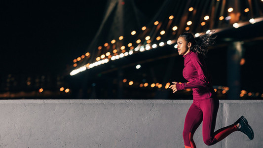 Mixed race woman in sports clothes running at night outdoors