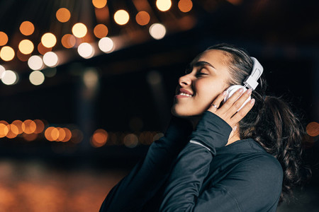 Woman in sports clothes with headphones enjoying music during training