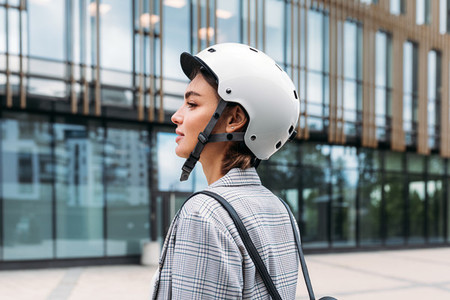 Side view of a young businesswoman wearing helmet standing outdoors near office building