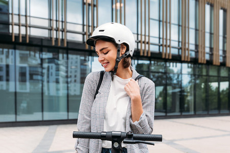 Beautiful smiling woman wearing helmet standing outdoors with an electric scooter in front of building