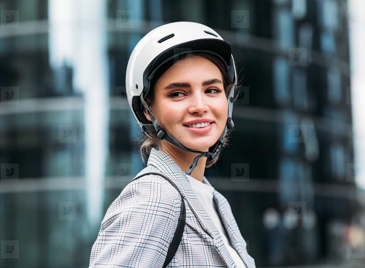 Portrait of a smiling woman wearing cycling helmet standing in front of an office building