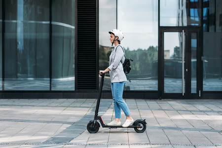 Side view of a young businesswoman riding electric push scooter  Female in cycling helmet driving electrical scooter against building