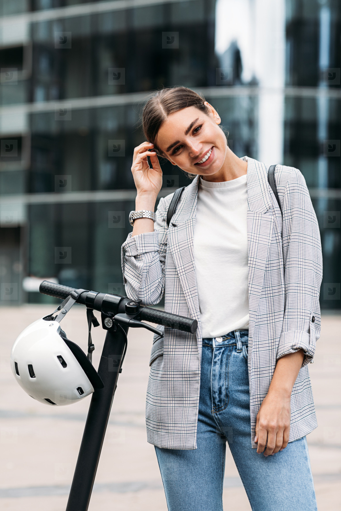 Smiling woman standing outdoors with electric scooter looking at camera