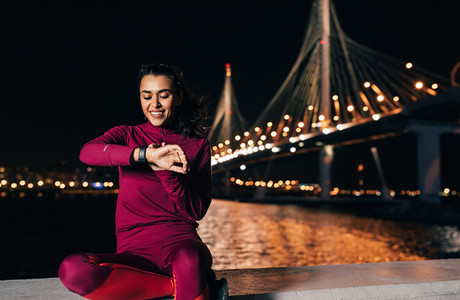 Young slim woman sitting on embankment checking smartwatch during training at evening