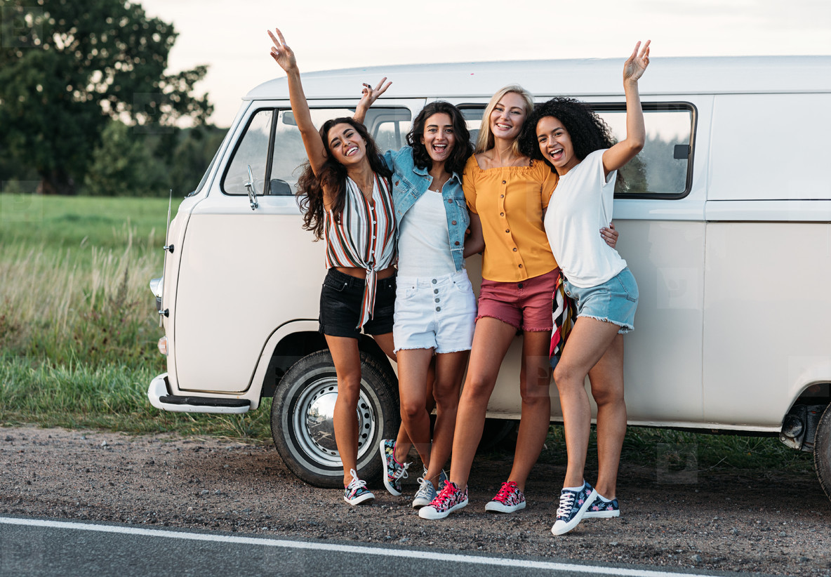 Happy diverse friends at camper van  Four smiling women standing together on the roadside near a car during vacation
