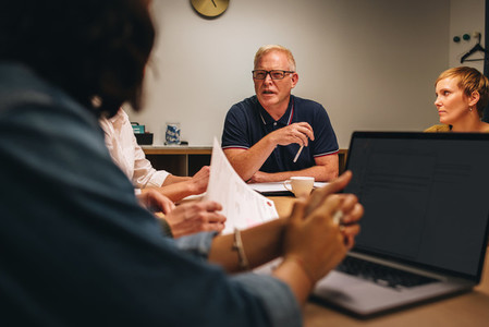 Senior man talking to colleagues in conference meeting