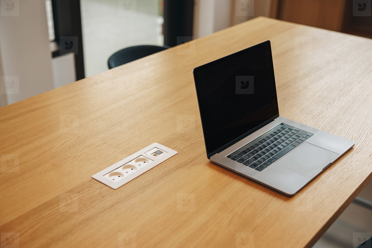 Laptop with blank screen in office conference room