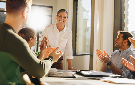 Team clapping in meeting for a woman colleague