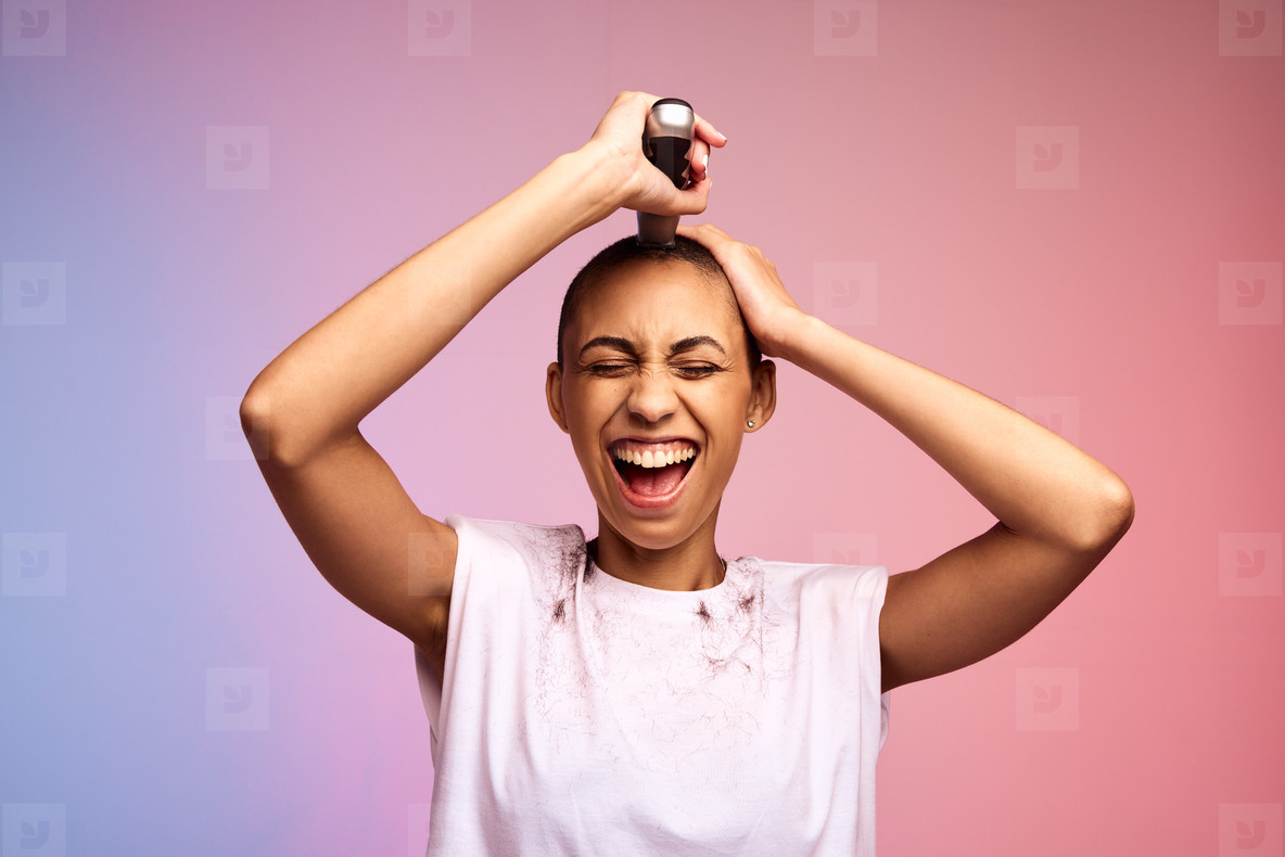 Happy woman trimming her head to bald