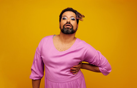 Drag queen posing on yellow background