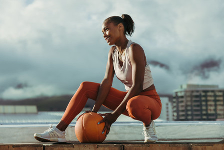 Fitness woman crouching with medicine ball
