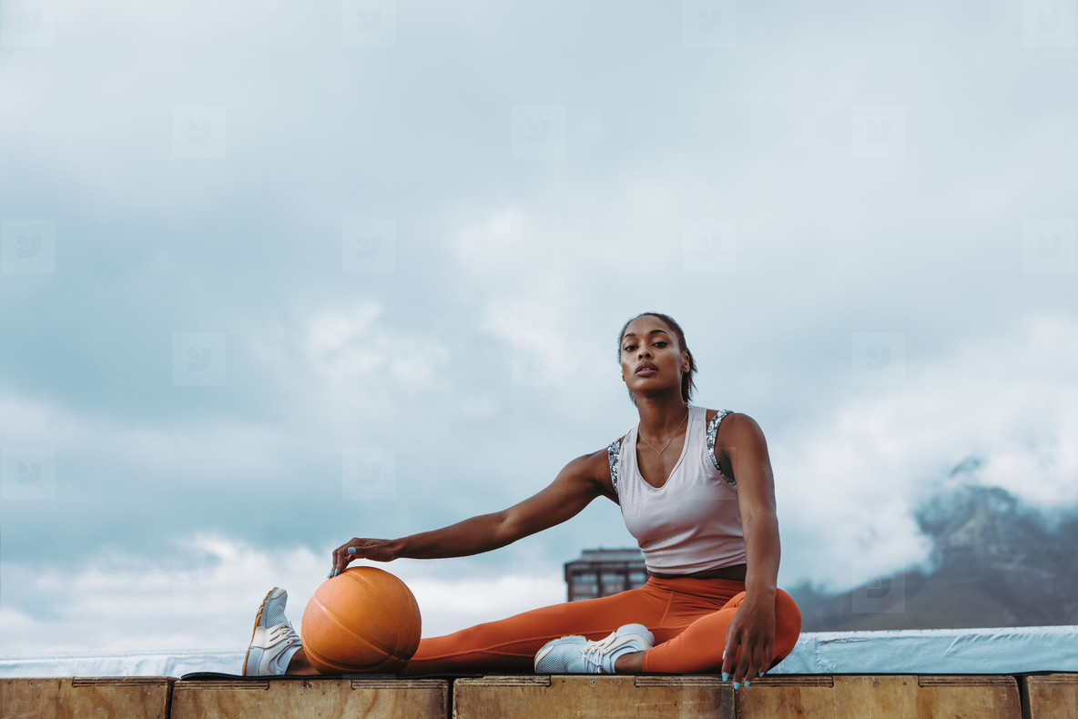 Athletic female taking break from workout on rooftop