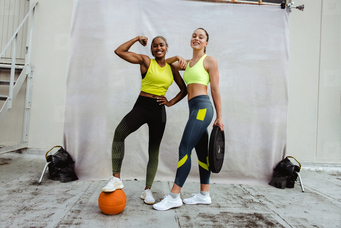 Two sports women with muscular body on rooftop