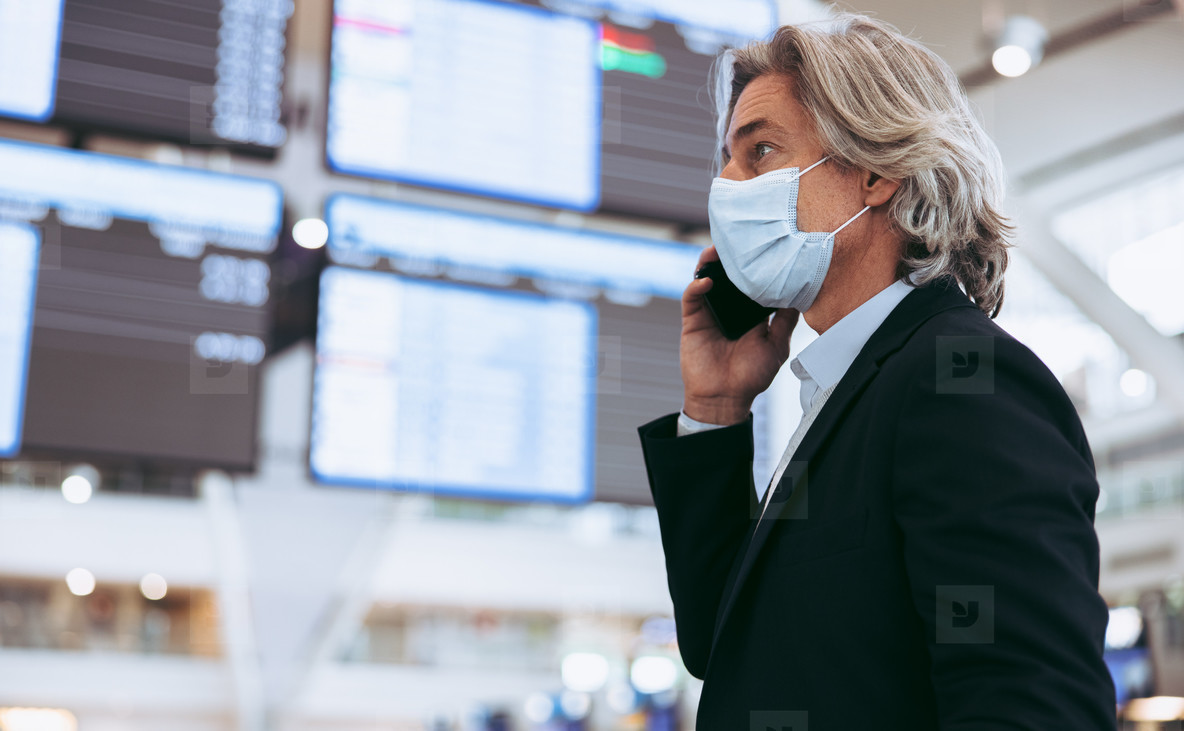 Man with face mask at airport terminal talking on phone
