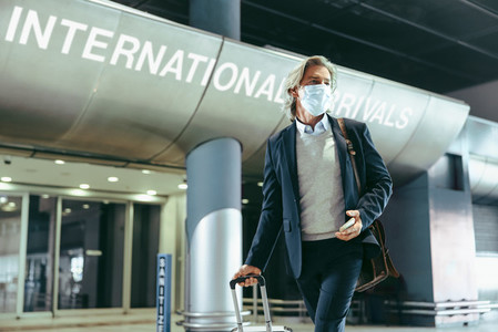 Business traveler with face mask at airport