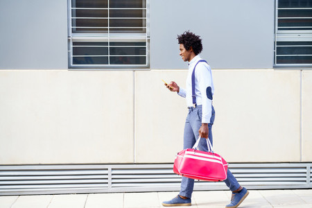 Black man with afro hairstyle carrying a sports bag and smartphone outdoors