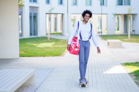 Black businessman riding skateboard near office building
