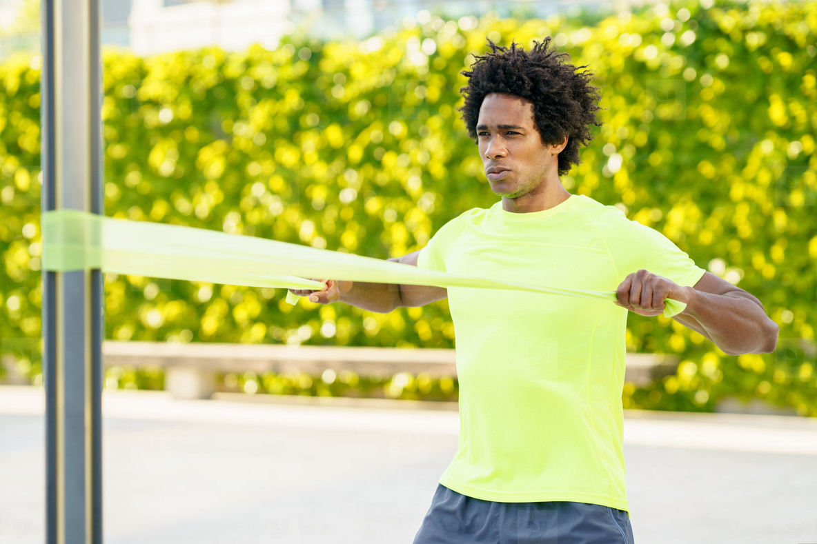 Black man working out with elastic band outdoors