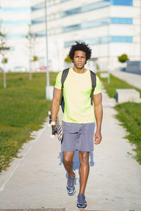 Black man going for a workout in sportswear and a skateboard