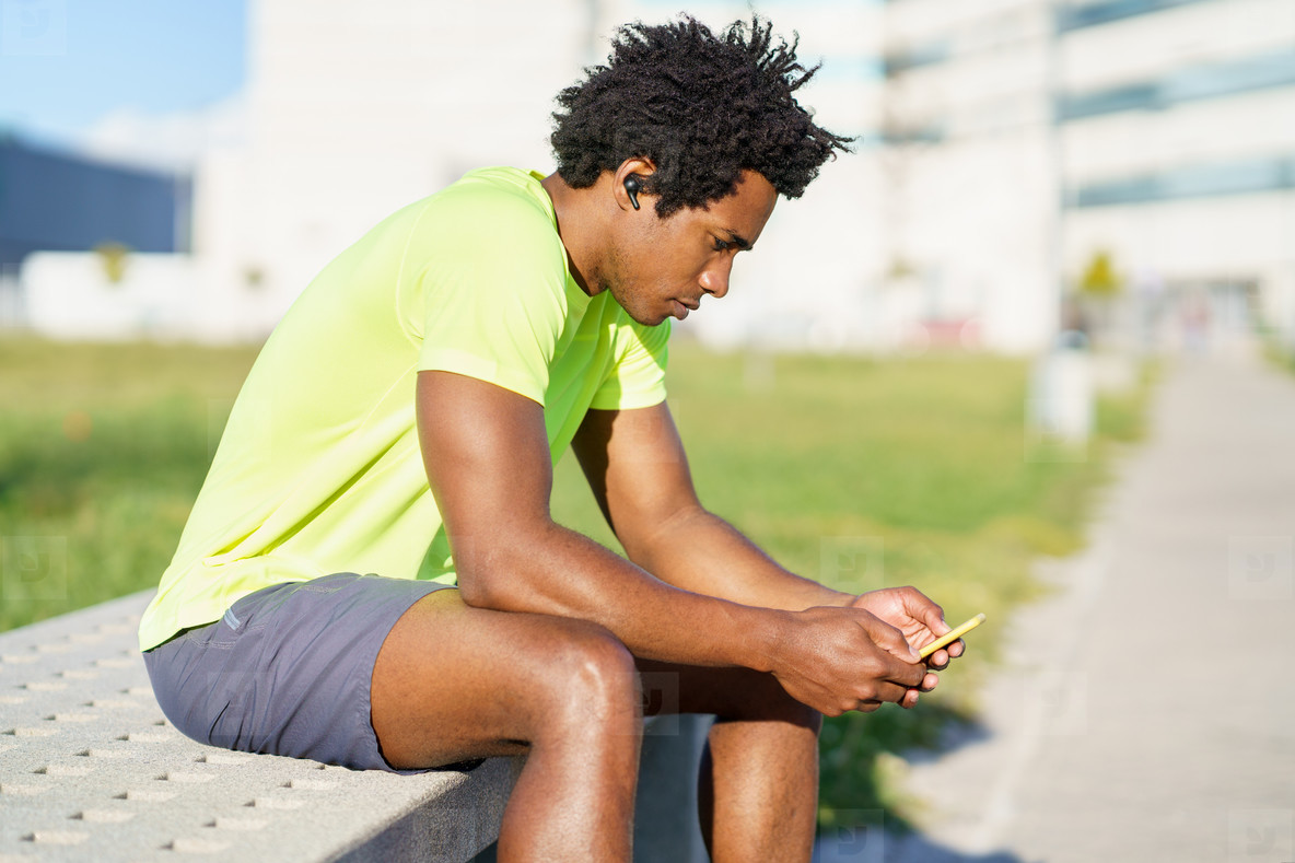 Black man consulting his smartphone with some exercise app while resting from his workout