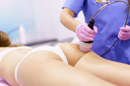 Woman receiving anti cellulite treatment with radiofrequency machine in a beauty center