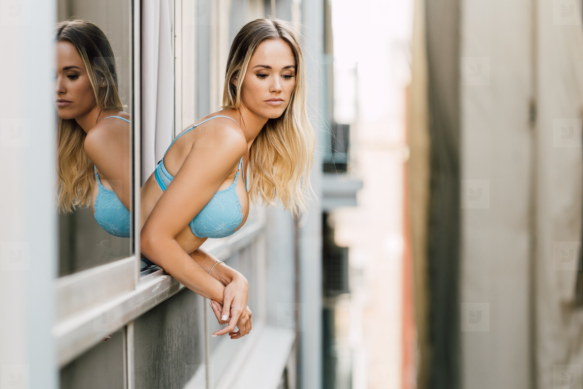 Young woman in lingerie leaning out the window of her room