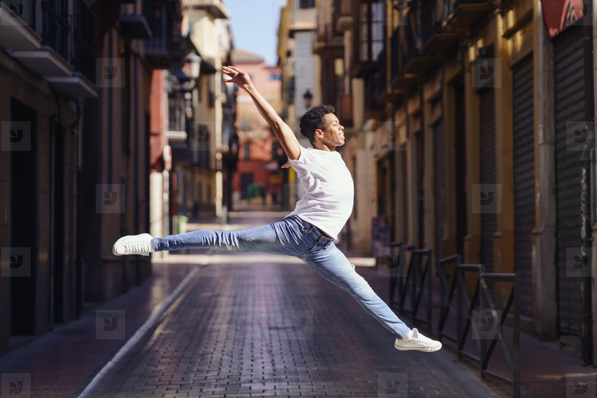 Young black man doing an acrobatic jump in the middle of the street