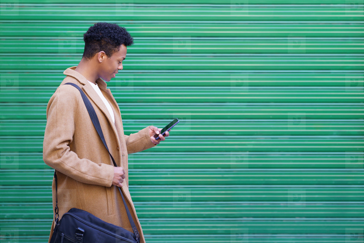 Black young man using a smartphone near a urban wall