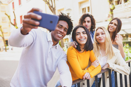 Multi ethnic group of friends taking a selfie in the street with a smartphone